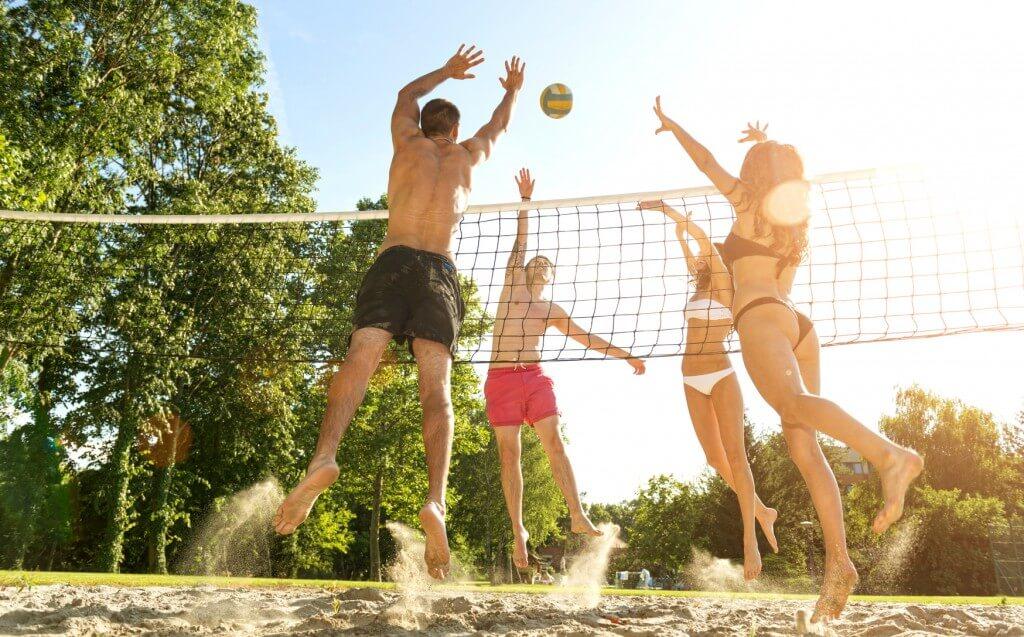 Freunde finden sich beim Sport und spielen Volleyball