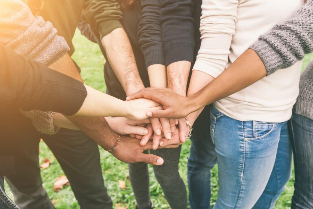 Freunde finden per Jugendarbeit Freunde reichen sich die Hand und bilden ein soziales Netz