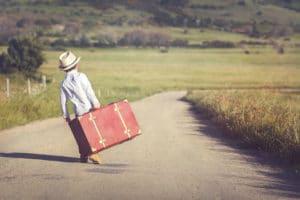 Keine Freunde. Einsamer Junge geht mit Koffer auf Straße.